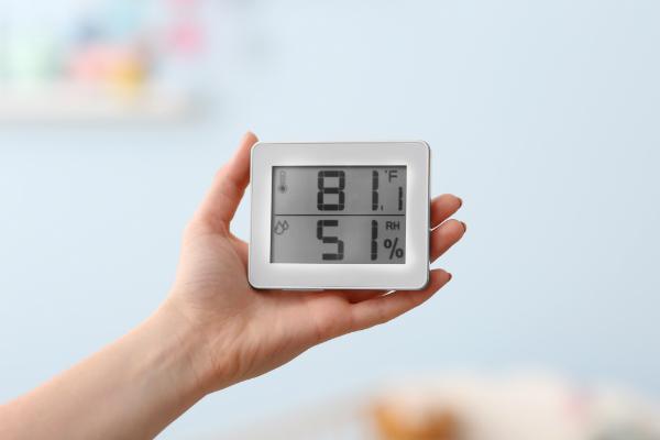 Frau ueberprueft die Temperatur und Feuchtigkeit im Babyraum