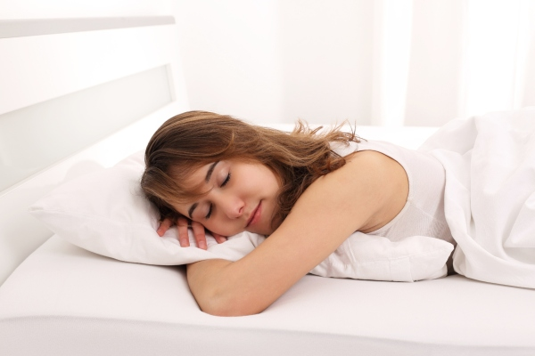 Junge Frau schlaeft im Bett mit Arm unter Kissen