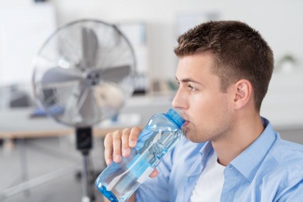 Mann trinkt Wasser im Buero