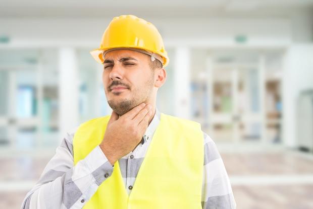 Arbeiter mit Helm fasst sich an den Hals