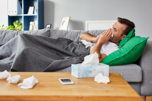 Mann liegt auf Couch und niest