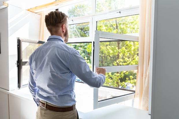 Mann macht Fenster auf