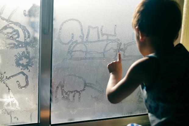 Junge am malt auf kondensiertem Fenster