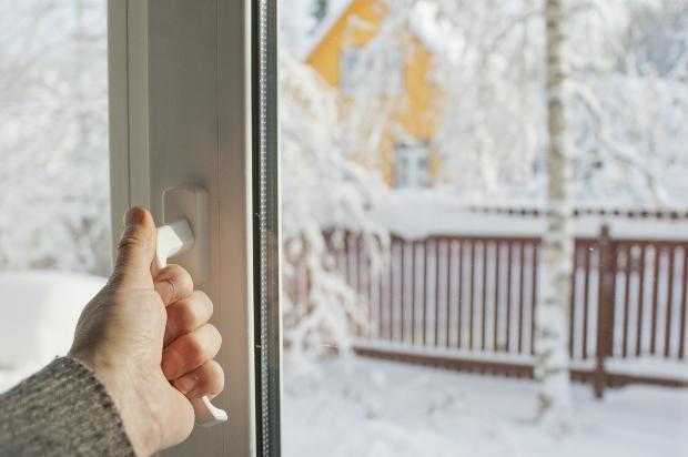 Hand greift zum Fenster, um es zu öffnen