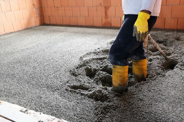 Mann steht mit Stiefeln im Estrich - Schimmel im Neubau droht