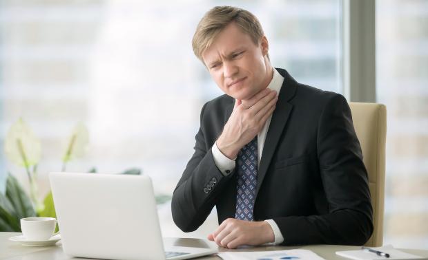 Mann in Anzug fasst sich an den Hals