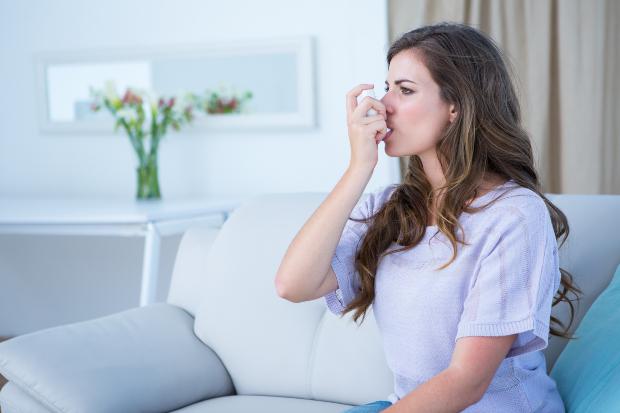 Frau mit Asthma Spray - roter Schimmel kann Asthma auslösen