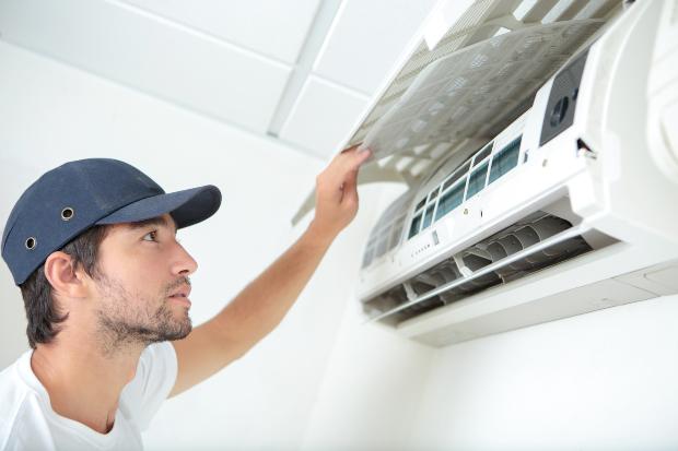 Mann prüft Klimaanlage