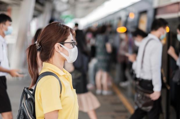 Junge Frau mit Atemschutzmaske im Zug