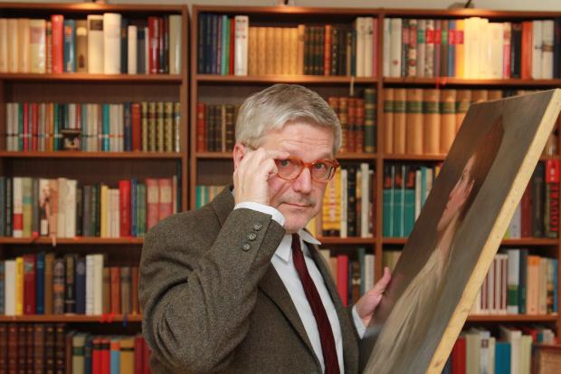 Experte steht vor einem Gemälde - sachgemäß Kunst lagern ist wichtig