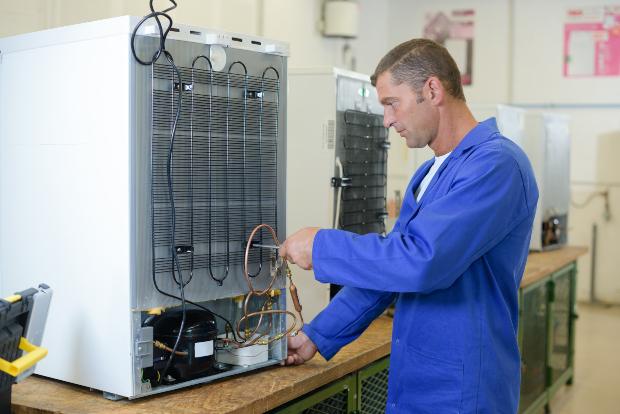Techniker arbeitet hinten an einem Kühlschrank
