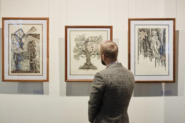 Mann betrachtet Bilder in einer Gallerie