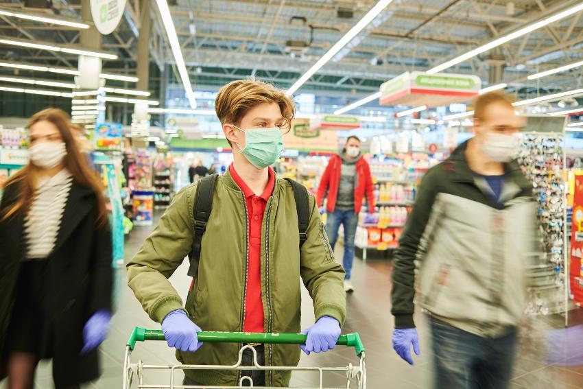 Menschen im Supermakt mit Mundschutzmasken - Aerosole werden aufgefangen