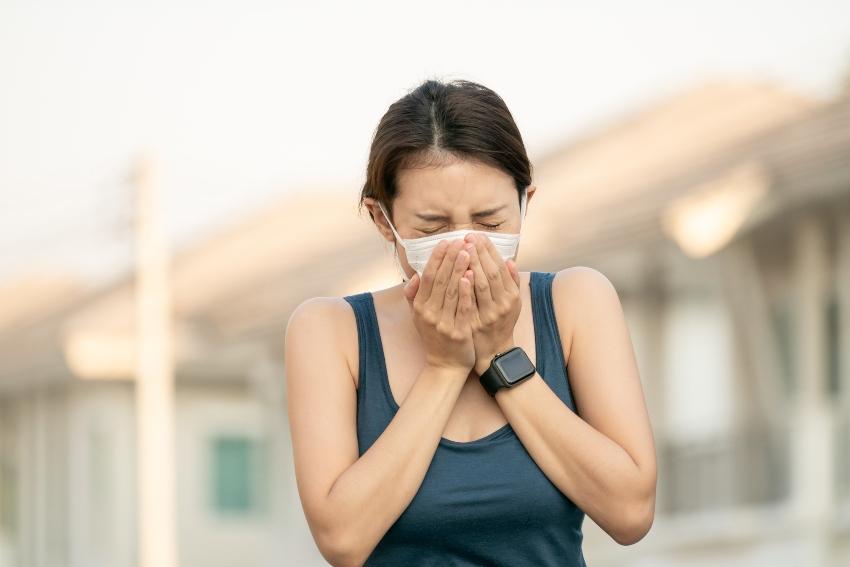 Frau niest in Schutzmaske - Aerosole bleiben in der Maske