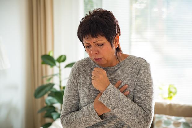 Frau hustet - Schimmelgeruch deutet auf Schimmelbefall in der Wohnung hin