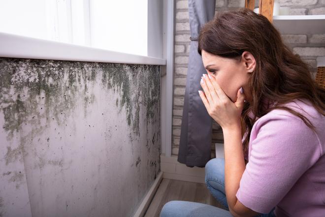 Frau hält sich die Hände vors Gesicht, Schimmel an der Wand