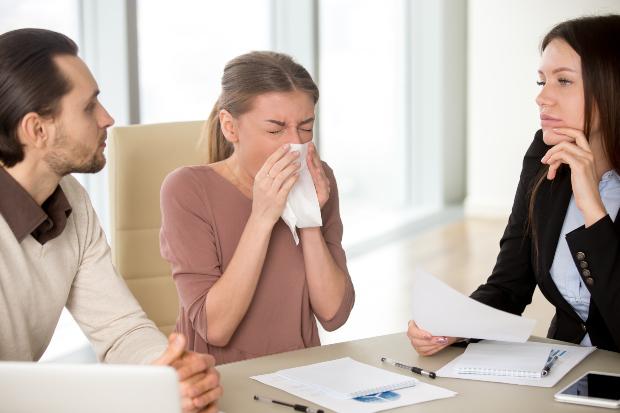 Junge Frau niest im Büro neben 2 Kollegen