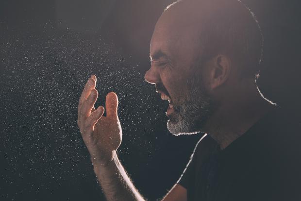 Mann niest, Gegenlichtaufnahme -Aerosole
