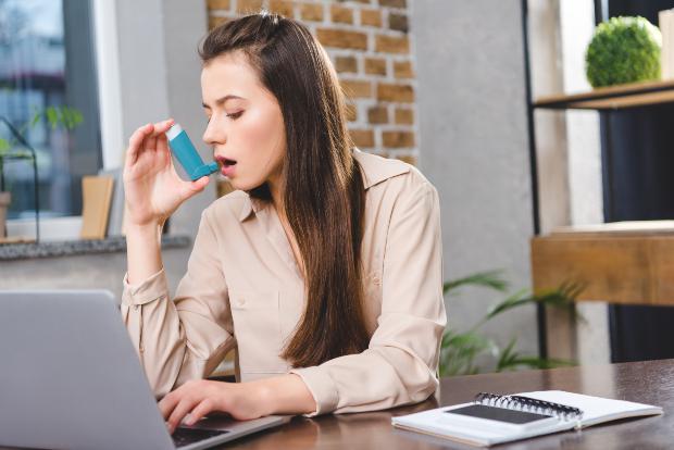 Frau am Schreibtisch mit Asthma-Spray