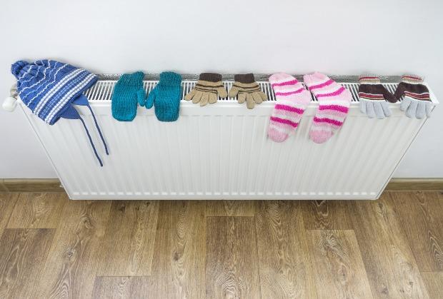 Socken, Handschuhe und Mütze liegen zum Trocknen auf einer Heizung - Kleidung in der Wohnung trocknen