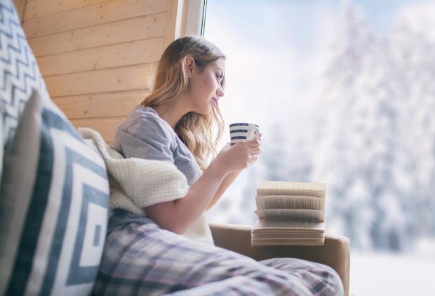 Junge Frau sitzt im Winter mit Becher Kaffee oder Tee am Fenster