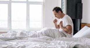 Mann sitzt hustend im Bett - Trockener Hals