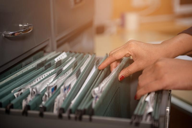 Archivarin sucht Dokument im Akten-Ablage