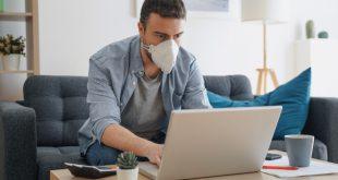 Mann mit Schutzmaske am Laptop - Virenkonzentration beachten
