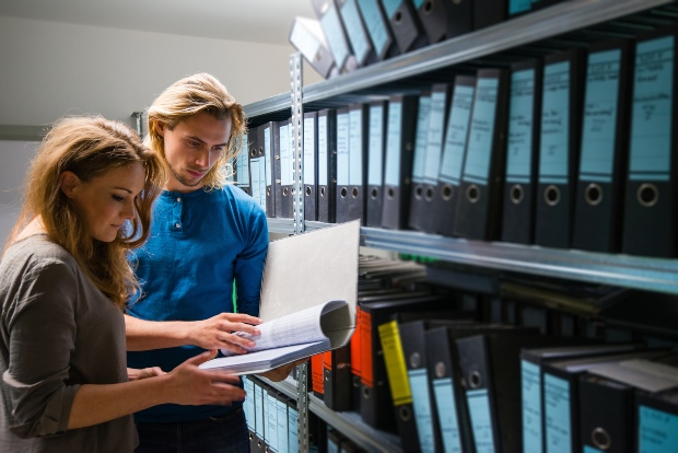 Zwei junge Leute lesen in archivierten Akten - die Luftfeuchtigkeit im Archiv muss stimmen
