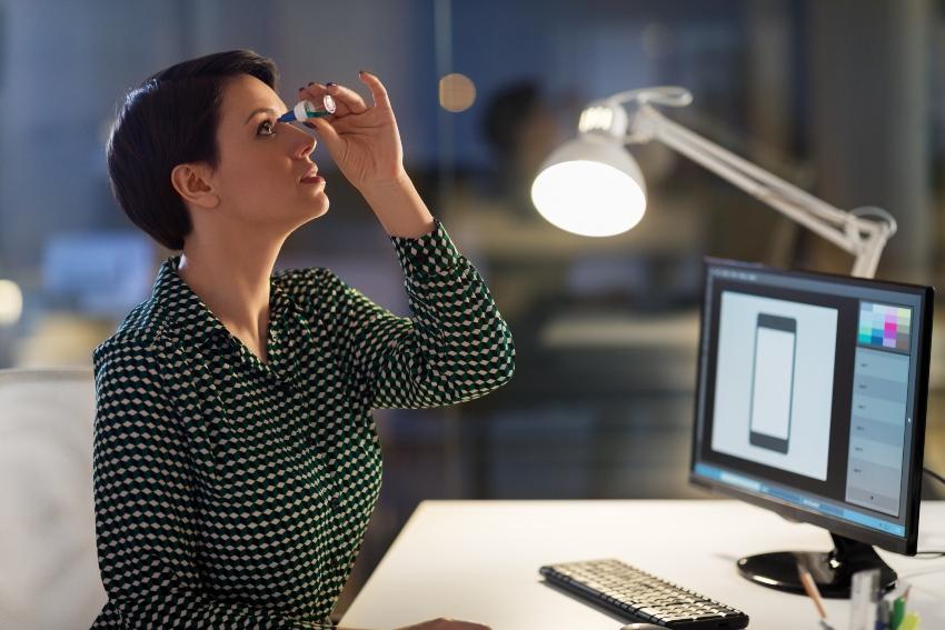 Junge Frau benutzt Augentropfen im Büro