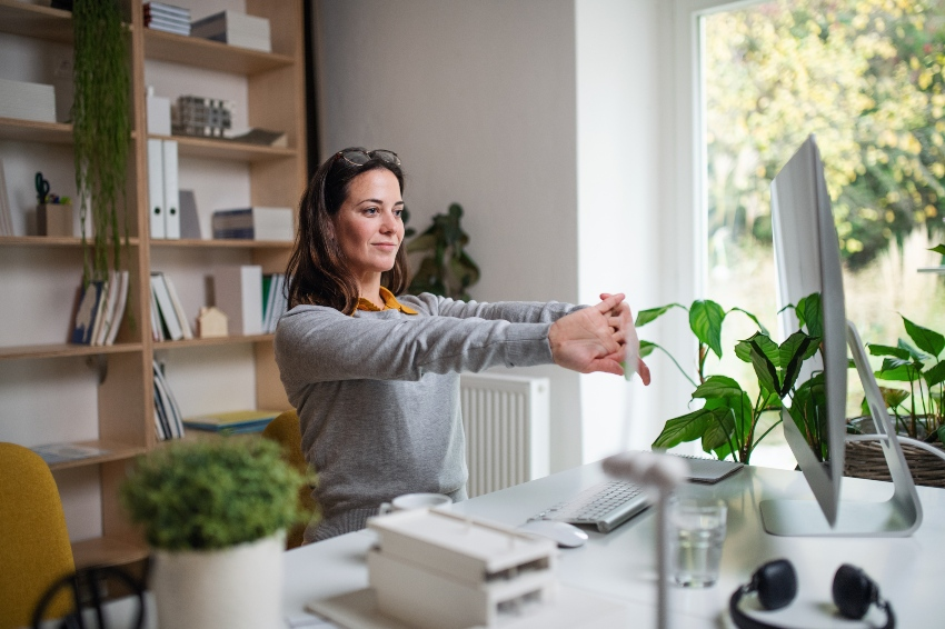 Junge Frau strecht im Home-Office