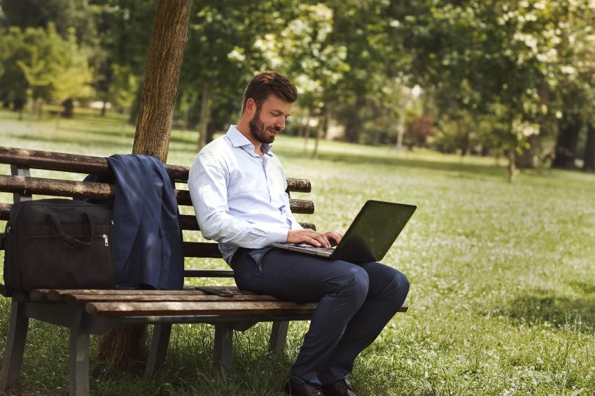 Junger Mann mit Laptop auf Park-Bank - mobiles Arbeiten ist nicht gleich Home-Office