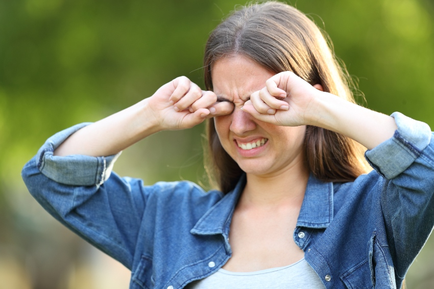 Junge Frau reibt sich die juckenden Augen - Pollenallergie tritt besonders im Frühling auf